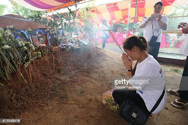 A woman pays her respects to prominent political analyst Kem Ley in front of his grave during a funeral ceremony in Takeo province to mark 100 days...