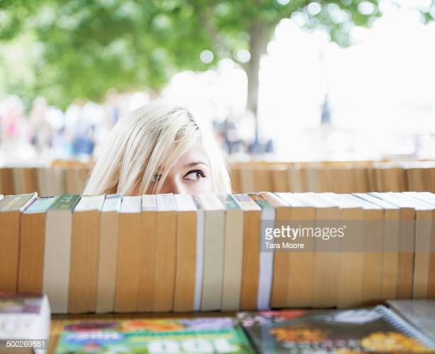woman peaking head over pile of books