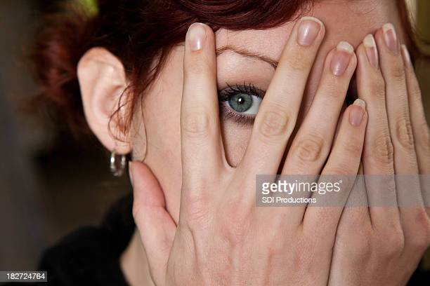 Woman Peaking Through Hands on her face