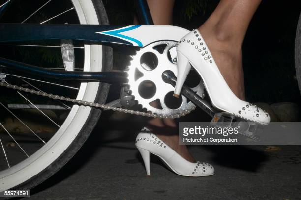 Woman pedaling a bicycle in high heels