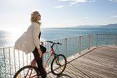 Woman pedals bike along waterfront railing, sea