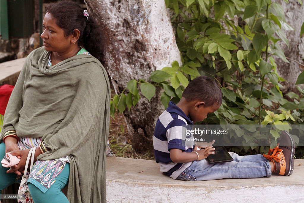 A woman pedestrian sits in the shadow of a way side tree as her kid playing with a mobile phone to pass the time in the eastern Indian city Bhubaneswar, India, Wednesday, 29 June 2016. Maximum people of the India are using smart phones for better communication and entertainment in their livelihood.