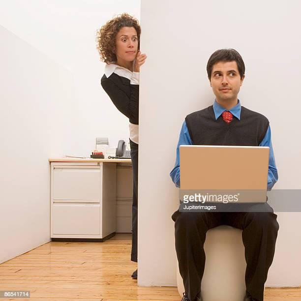 Woman peeking around cubicle at man with laptop