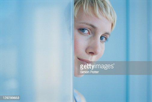 Frau Spähen durch die Tür. Sie trägt : Stock-Foto