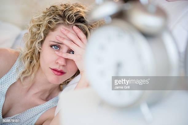Woman peeking at alarm clock