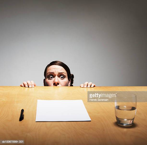 Woman peeking from behind table