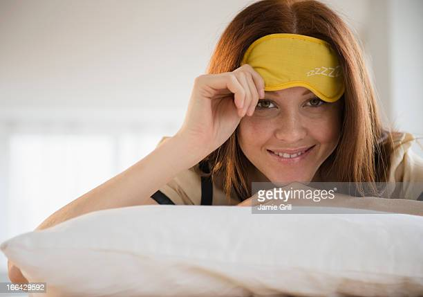 Woman peeking from sleep mask
