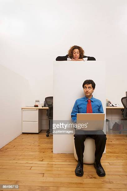 Woman peeking over cubicle at man with laptop