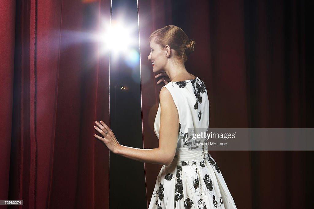 Woman peeking through theatre curtains