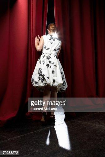 'Woman peeking through theatre curtains, rear view'