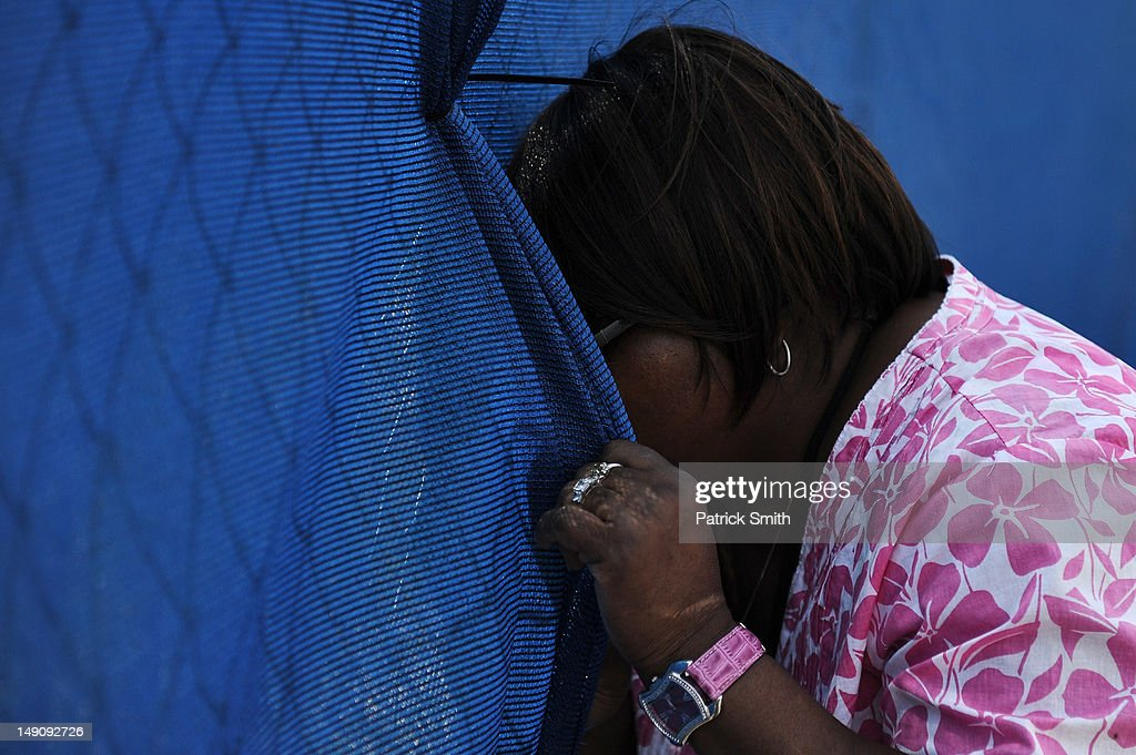 A woman peeks a view through the tarp at the site where the statue of former Penn State University football coach Joe Paterno once stood outside Beaver Stadium on July 22, 2012 in State College, The statue was removed by workers after Pennsylvania. Penn State's president Rodney Erickson made the decision Sunday in the wake of the child sex scandal of former assistant football coach Jerry Sandusky. According to an FBI report, it is believed that Paterno had detailed knowledge of Jerry Sandusky sexually abusing children before and after Sandusky retired from coaching at Penn State.