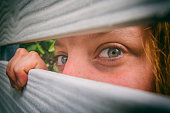 Woman peeks through the neighbours fence