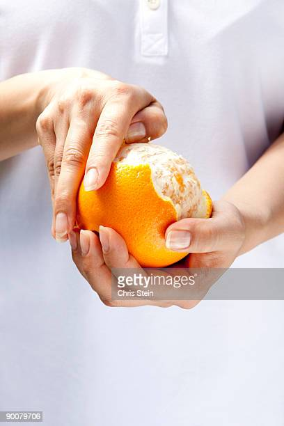Woman peeling an orange