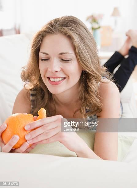 Woman peeling orange, smiling