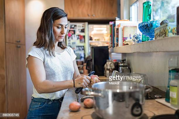 Woman peeling potato at kitchen counter