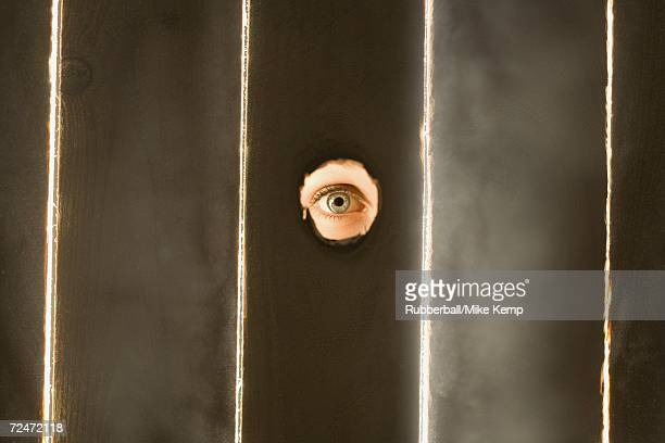 Woman peeping through hole in fence