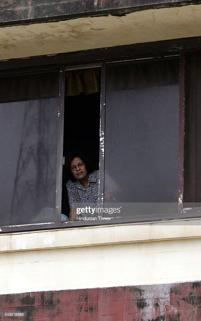 A woman peeps through the window from where Leela Ramchand (80) wife of late ex-skipper of Indian Cricket team Gulabrai Ramchand committed suicide on Friday at Sports field building, Worli on July 22, 2005 in Mumbai, India.