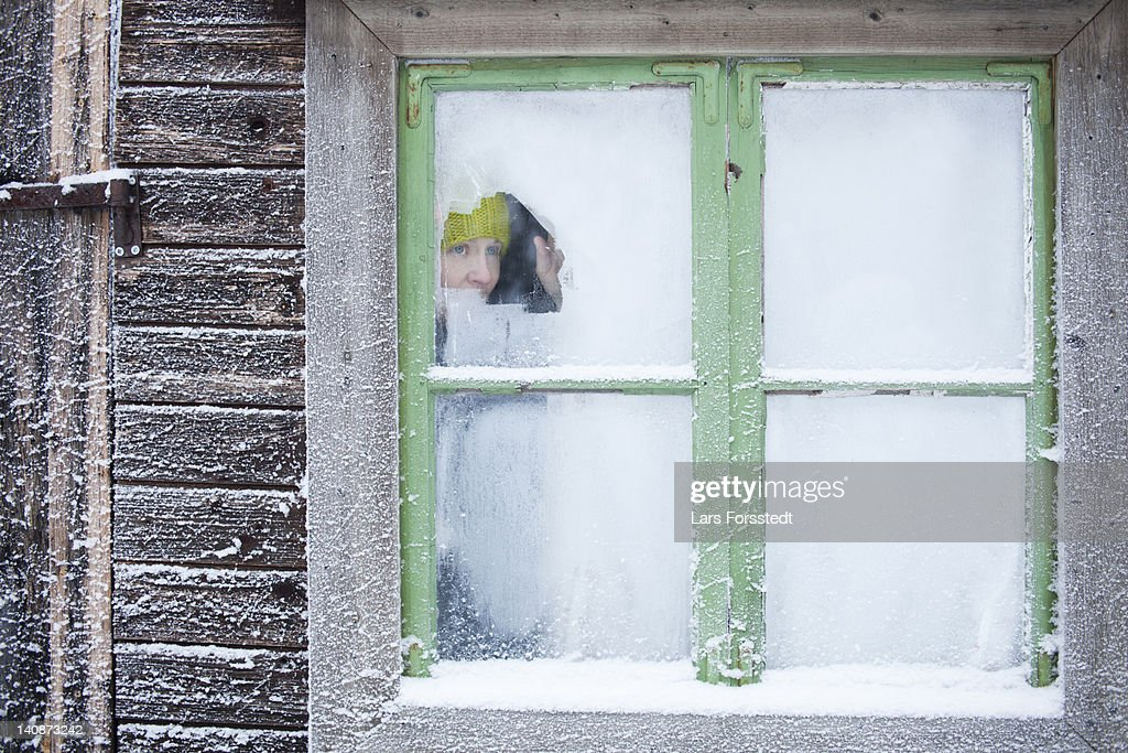 Woman peering out frosty window : Stock Photo