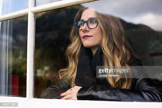 A woman peering outside from a window.