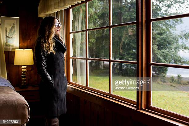 A woman peering outside from a window.