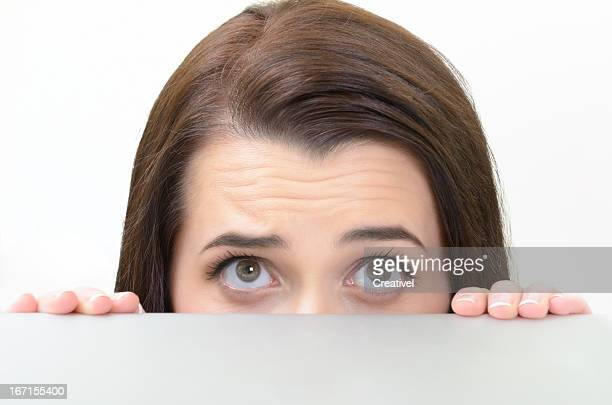 Woman Peering over Edge of Table