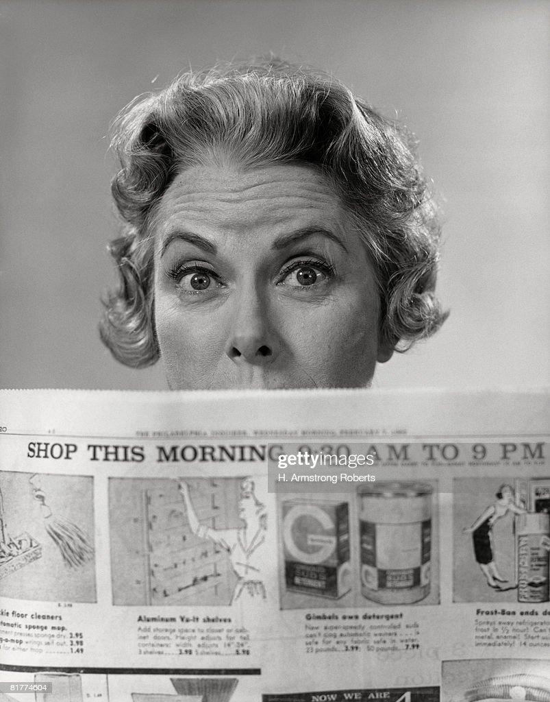 Woman peering over newspaper. : Stock Photo