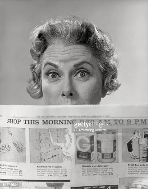Woman peering over newspaper.