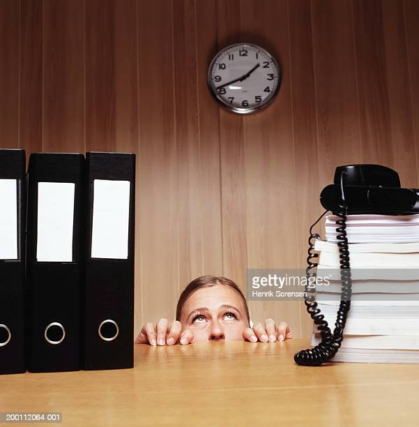 Woman peering over office desk, high section