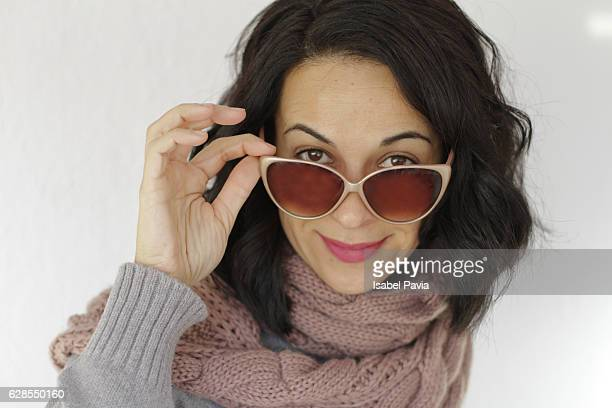 Woman peering over sunglasses