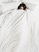 Woman peering over the top of bed sheet