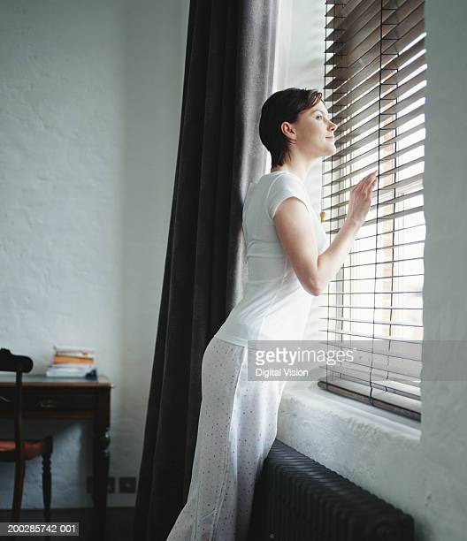 Woman peering through blinds, side view