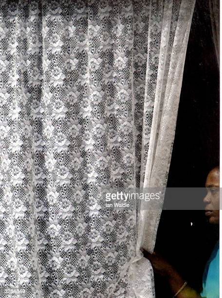 A woman peers from her window as members of the extreme rightwing group the National Front hold a demonstration at Finsbury Park Mosque April 9 2004...