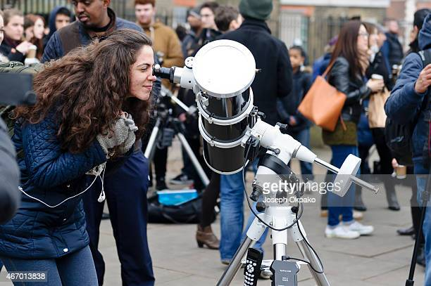 A woman peers through a powered telescope to watch a partial solar eclipse from Greenwich park on March 20 2015 A partial eclipse of varying degrees...