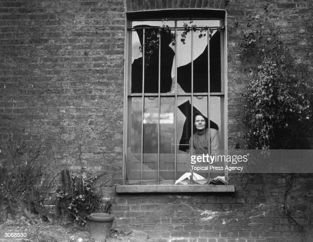 A woman peers through a shattered window in Holloway prison after an explosion by suffragettes who had tried to blow the place up