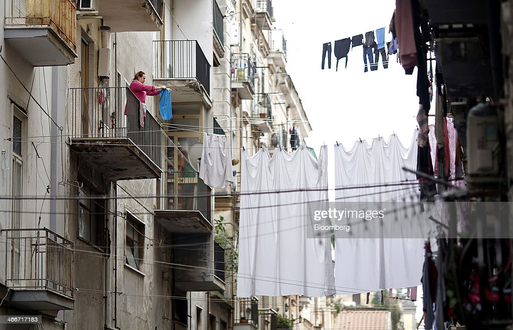 A woman pegs an item of clothing to a washing line from the balcony of a residential apartment block above a side street in Naples, Italy, on Saturday, Feb. 1, 2014. In Naples, the local youth unemployment rate in 2012 was 53.6 percent compared to a national average of 35.3 percent. Photographer: Alessia Pierdomenico/Bloomberg via Getty Images