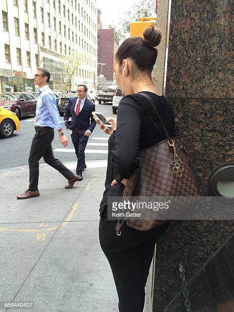 A woman perched on the sidewalk near the corner of a building wall looking down at her cell phone while the busy city afternoon activity swirls...