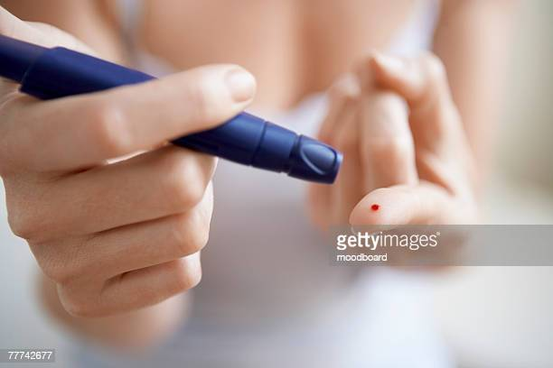 Woman Performing Blood Test on Herself