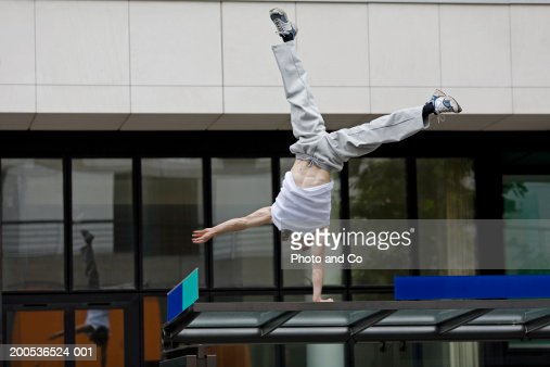 Woman performing cartwheel on top of bus shelter
