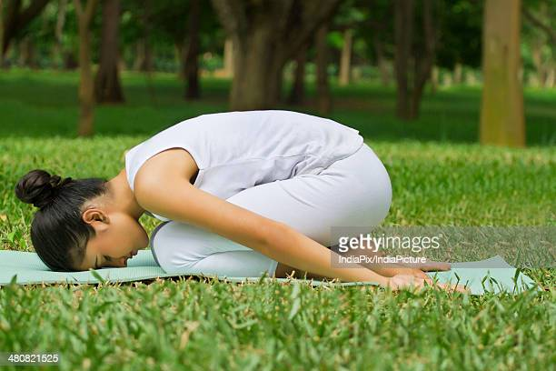 Woman performing childs pose on mat at park