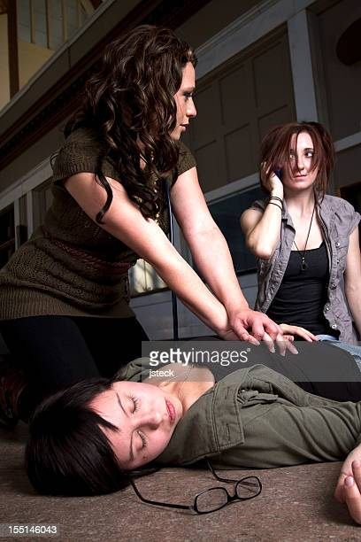 Woman performing CPR on an unconscious woman