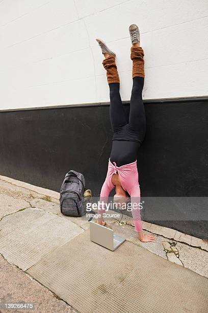 Woman performing handstand and using laptop on pavement