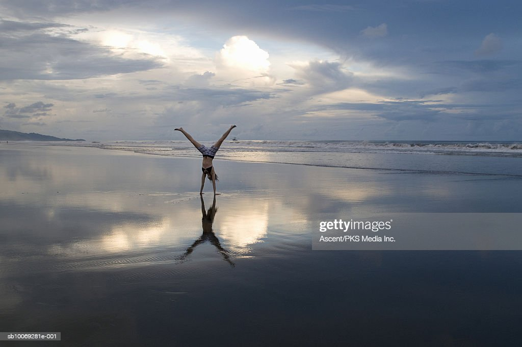 Woman performing handstand on beach at sunset : Stock Photo