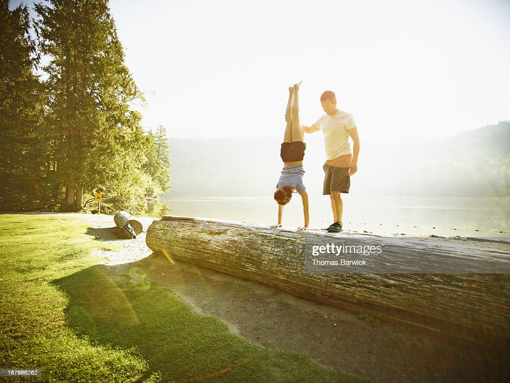 Woman performing handstand on log on lakeshore
