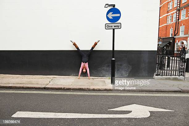Woman performing handstand on pavement