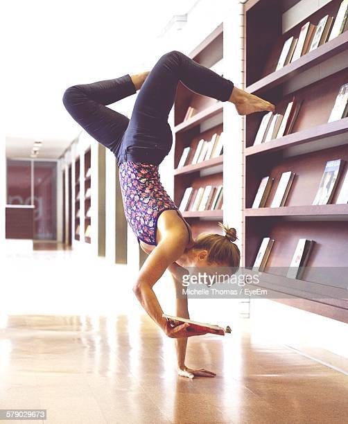 Woman Performing Handstand While Reading Book In Library