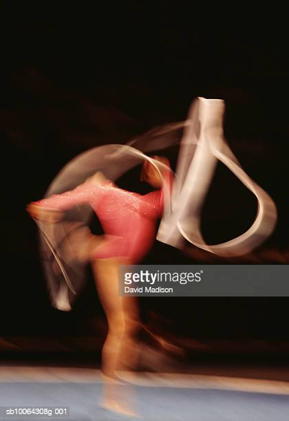 Woman performing rhythmic gymnastic, twirling ribbon