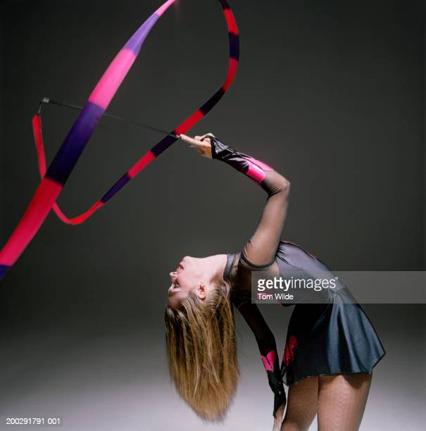 Woman performing rythmic gymnastics bending backwards twirling ribbon