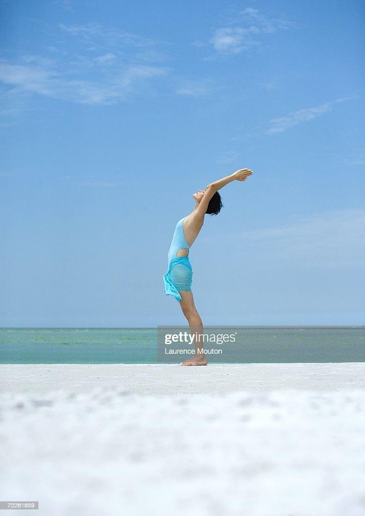 Woman performing sun salutation on beach