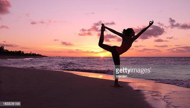 A woman performing yoga on the beach at sunset