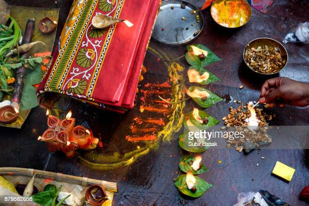 A woman performs her ritual at Chhat festival in front of fire and trays full of fruits and earthen lamps.